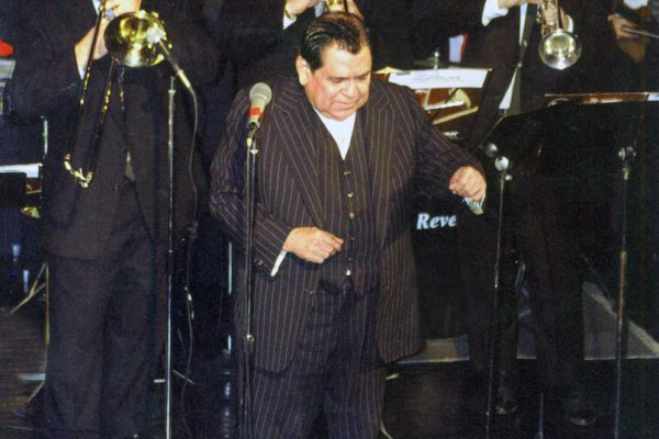 Front of band Latin music icon, singer Vitín Avilés, left to right: Mike Molina - bongo bell, Demetrios Kastaris - trombone, Jose Mercado - trumpet, Steve Gluzband - trumpet, right corner: Alí Bello - violin, The Point CDC in the Bronx, New York, February 4, 2000. Tribute concert to Vitín Avilés.
